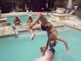 Chica en bikini se cae haciendo acrobacia en la piscina